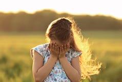La cubierta unhaapy gritadora de la muchacha del niño hace frente a las manos en la naturaleza del verano Fotos de archivo libres de regalías