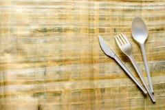 La cuchara, la bifurcación y el cuchillo plásticos están en el papel del papiro fotografía de archivo