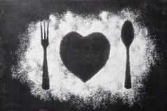 La cuchara, la bifurcación y la placa en corazón forman, flour asperjado alrededor de foto de archivo libre de regalías