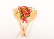La cuchara de la bifurcación en el fondo blanco con chilis candentes sazona con pimienta tapa Foto de archivo