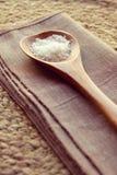 La cuchara de madera de la sal del mar forma escamas por completo en fondo rústico Imágenes de archivo libres de regalías