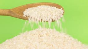La cuchara de madera vierte el arroz de los granos en el montón del arroz en una pantalla verde almacen de metraje de vídeo