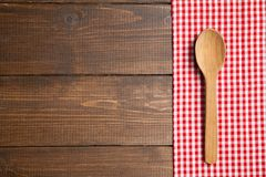 La cuchara en la tabla de madera con rojo comprobó el mantel Imagen de archivo libre de regalías