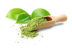 La cucharada con té y verde del matcha se va en el fondo blanco imagen de archivo libre de regalías