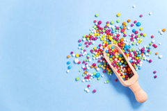 La cucharada de madera con el caramelo coloreado encendido, azúcar comestible colorido gotea Imagenes de archivo