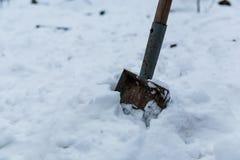 La cucharada oxidada cansada vieja de la pala del jardín en mi patio trasero tiene relajarse en nieve en invierno Fotografía de archivo libre de regalías