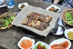 La cucina coreana del barbecue con i piatti laterali è servito sulla tavola fotografia stock libera da diritti
