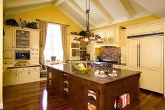 La cucina di legno gialla lussuosa con l'isola marrone ed il granito completano Fotografie Stock Libere da Diritti