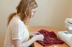 La cucitrice attraente che si siede alla tavola con la macchina per cucire e ricama la maglia rossa in studio fotografia stock
