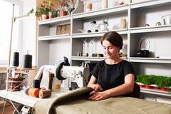 La cucitrice cuce i vestiti Posto di lavoro del sarto immagine stock
