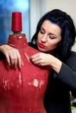 La cucitrice ripara il vecchio mannequin rosso Fotografie Stock
