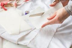 La cucitrice sta tagliando il disegno per un vestito con le forbici Fotografia Stock Libera da Diritti
