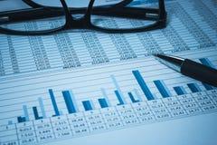 La cuenta bancaria financiera del banco que considera almacena datos de la hoja de cálculo con los vidrios en contable azul Imagen de archivo libre de regalías