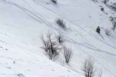 La cuesta de la montaña coronada de nieve rayada con las pistas del esquí foto de archivo libre de regalías
