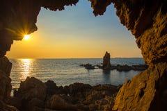 La cueva cerca del mar en la puesta del sol Foto de archivo