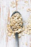 La cuillère avec l'avoine s'écaille sur le fond en bois blanc Photo libre de droits