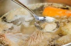La cuillère de fer enlève la mousse du bouillon Image libre de droits