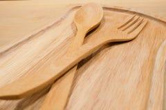 La cuillère et la fourchette en bois est placée sur le plat photographie stock libre de droits