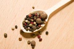 La cuillère a rempli de grains de poivre sur une surface en bois Images stock