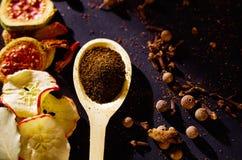 La cuillère rustique en bois de plan rapproché s'est remplie de poudre fraîche de tisane, d'autres thés et d'épices à l'arrière-p Image libre de droits