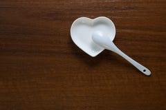 La cuillère se trouve d'un plat blanc sous forme de coeur sur un fond en bois Plats élégants en céramique sur une table d'écrou C photos stock