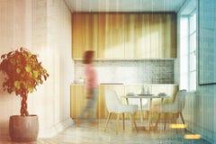 La cuisine blanche, les partie supérieure du comptoir en bois affrontent, fille Photographie stock libre de droits