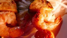 La cuisine de fusion chinoise thaïlandaise, nouilles avec des crevettes roses a fait frire sur des brochettes closeup