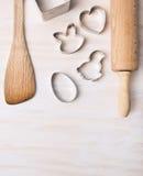 La cuisine font des ustensiles cuire au four avec des coupeurs de biscuit de Pâques sur le fond en bois blanc, vue supérieure photographie stock