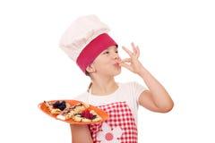 La cuisinière de petite fille avec des crêpes et la main correcte signent photo libre de droits