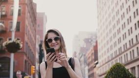 La cuisson étonnante a tiré de la jeune femme de touristes caucasienne enthousiaste avec le smartphone dans des lunettes de solei clips vidéos