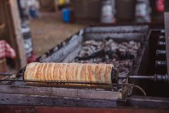 La cuisson de Kurtoskalacs, le gâteau hongrois traditionnel de broche, dans une boutique de pâtisserie E photographie stock libre de droits