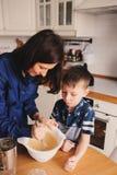 La cuisson de mère et de fils durcissent dans la cuisine Capture occasionnelle de mode de vie de la cuisson de famille Photographie stock