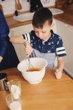 La cuisson de mère et de fils durcissent dans la cuisine Capture occasionnelle de mode de vie de la cuisson de famille Photos libres de droits
