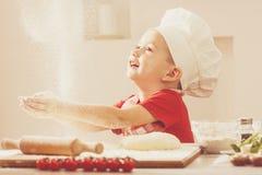 La cuisson de la pizza est amusement - petit chef jouant avec de la farine Photo stock
