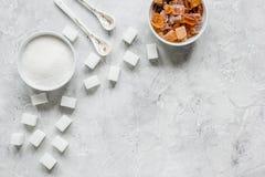La cuisson des bonbons a placé avec différents morceaux de sucre sur la maquette grise de vue supérieure de fond de table Photo stock