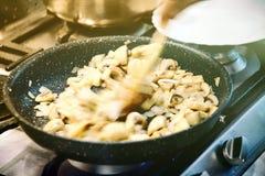 La cuisson du champignon de paris répand à l'oignon dans la casserole Photo stock