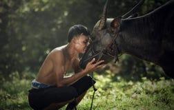 La cura asiatica dell'agricoltore fa il bufalo d'acqua di amore Fotografie Stock Libere da Diritti