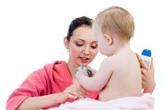 La cura della madre dopo il bagno alla neonata Immagini Stock