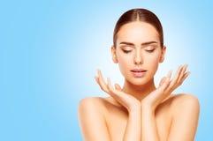 La cura di pelle di bellezza delle mani e del fronte, donna naturale compone, modella sul blu fotografia stock