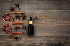 La cura di pelle e si rilassa Cosmetici e concetto di aromaterapia Olio di cannella sul copyspace di legno scuro di vista superio fotografia stock