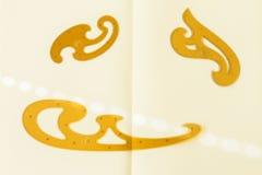 La curva francesa, beige y marrón colorea, en el fondo de papel, el instrumento de dibujo del ` s del diseñador Concepto de nuevo imagen de archivo libre de regalías