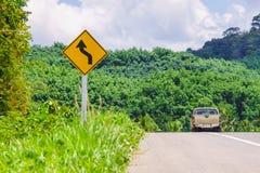 La curva inversa d'avvertimento ha lasciato il segnale stradale con il camion di raccolta sulla strada Fotografia Stock