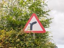 La curva roja de la advertencia del triángulo en camino para arriba a continuación firma licencia del metal del polo Fotos de archivo libres de regalías