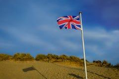 La curvatura insabbia la bandiera di spiaggia fotografia stock libera da diritti