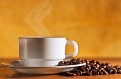 La cuvette blanche de café chaud avec la vapeur est sur la table Photographie stock libre de droits