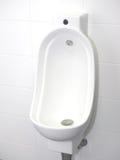 La cuvette d'urinoir avec les mains automatiques libèrent à affleurement dans des toilettes immaculées Photo stock