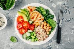 La cuvette de Bouddha avec de la salade d'épinards, quinoa, a rôti des pois chiches, poulet grillé, avocat, tomates, concombres,  image stock
