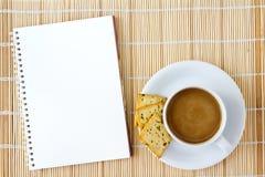 La cuvette de café chaud et le croquis blanc réservent sur un couvre-tapis Images stock