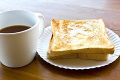 La cuvette de café et pleuvoir à torrents le pain grillé de lait Photo stock