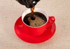 La cuvette de café rouge a rempli d'expresso noir Image libre de droits